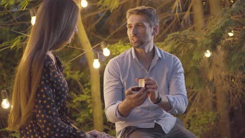 Handsome Caucasian Man Asking Girlfriend for Marriage and Giving Wedding Ring. Portrait of Happy
