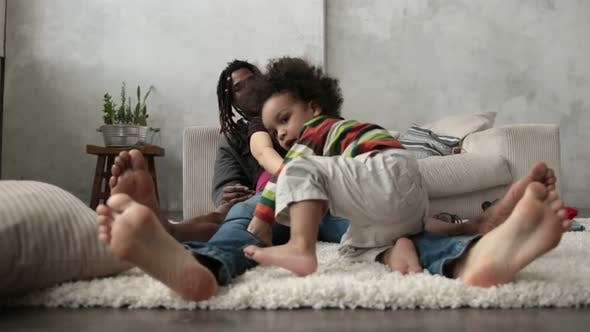 Thumbnail for Happy Interracial Family Sitting Barefoot on Floor