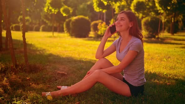 Thumbnail for Cheerful Female Chatting By Mobile in Garden