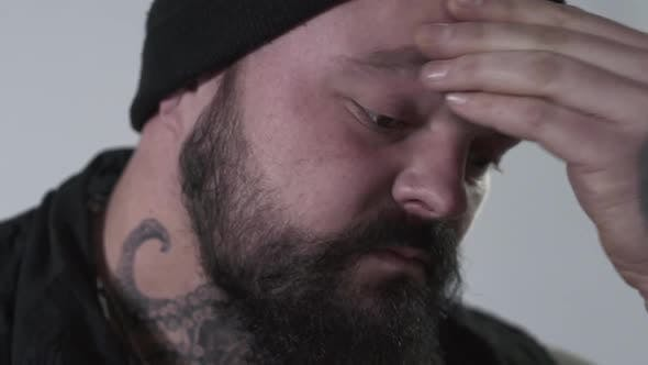 Aggressive Bearded Man Rubbing His Forehead To Hold Back Emotions. The Brutal Guy with Tattoos on