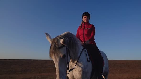 Thumbnail for Girl Sitting on a Horse Looks Into the Distance in the Field Against a Sky
