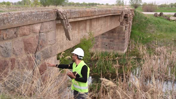 Engineer Examines the Road Bridge