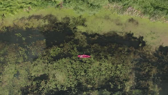 Thumbnail for Woman kayaking on red boat. Female floating in boat on river, top drone view.