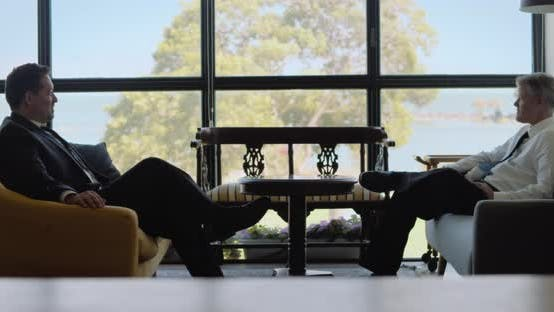 Two men in suits having a business meeting, they sitting near a big window on boutique sofas