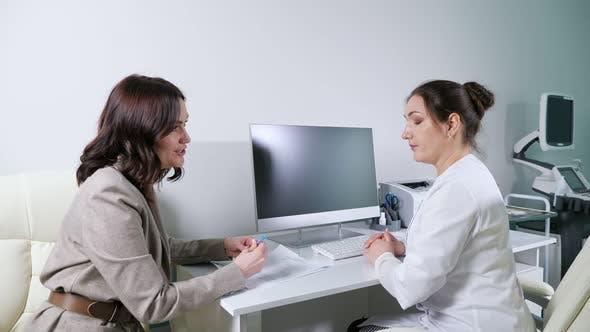Doktor in Robe hört Patienten am Tisch mit Computer zu