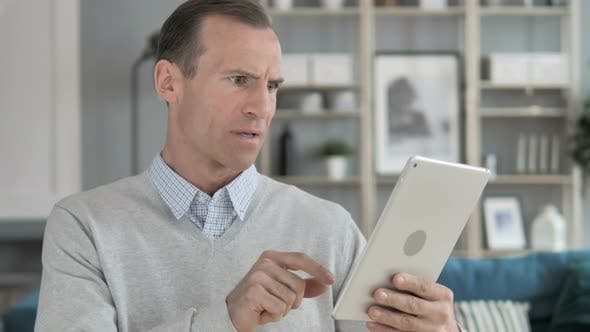 Thumbnail for Middle Aged Man Reacting to Loss while Using Tablet