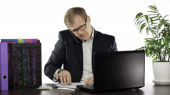 Thumbnail for Businessman Working in Office. Talking Loudly on Telephone While Reading Papers