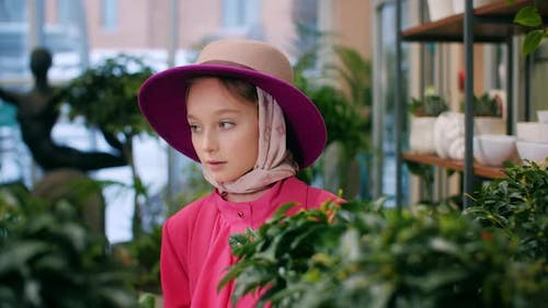 Young Cute Girl in Hat and Pink Jacket Looking Green Plants in Orangery