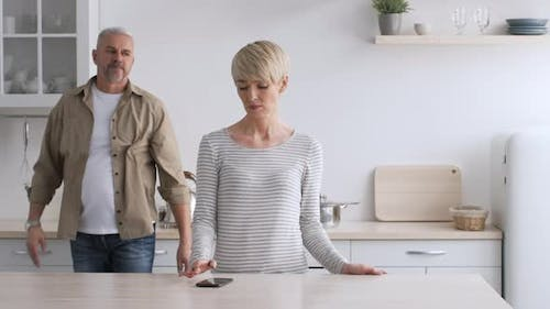 Husband Hugging Offended Wife Reconciling After Quarrel Standing In Kitchen