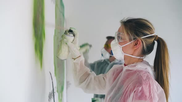 Thumbnail for Girl and Boyfriend in Workwears Paint Wall with Green Spray