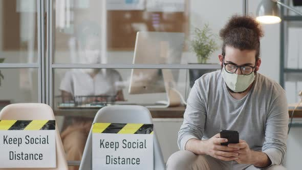 Thumbnail for Man in Face Mask Using Smartphone in Office during Coronavirus Outbreak