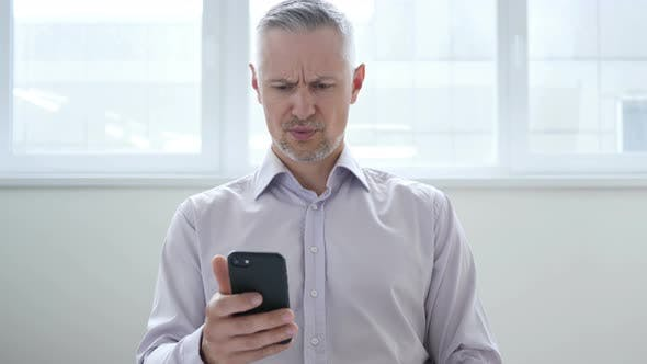 Shocked, Astonished Middle Aged Businessman Using Smartphone