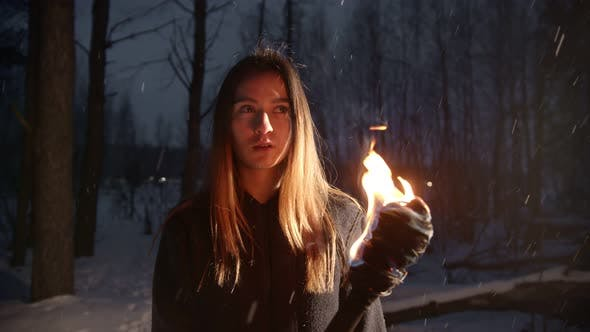 Thumbnail for Young Woman with Torch Standing in Winter Forest Under the Snowfall