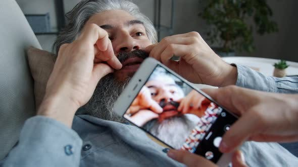 Closeup of Female Hands Using Smartphone to Take Pictures of Funny Mature Man Posing with Funny