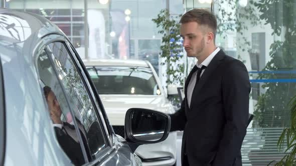 Thumbnail for Young Businessman in a Suit Examining Cars for Sale at the Dealership