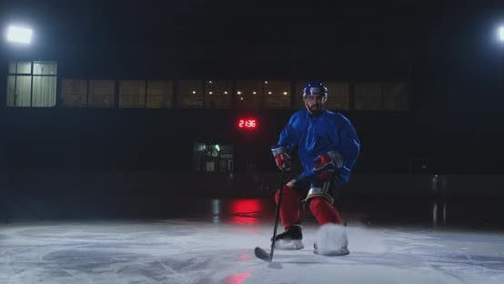 Thumbnail for Man Hockey Player in Hockey Uniform Leaves with a Stick in His Hands Out of the Darkness and Looks