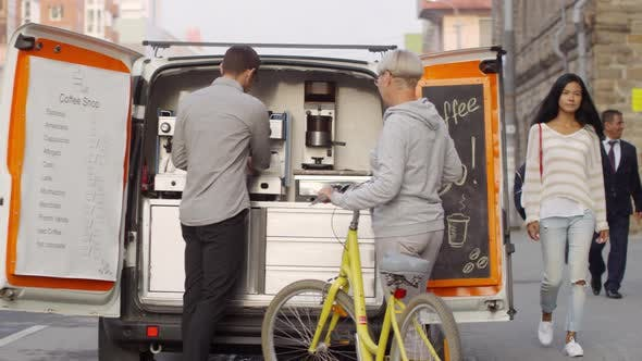 Mobile Coffee Van Seller Serving Espresso to Lady with Bicycle