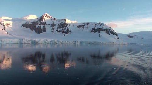 Sunset in Antarctica, with calm sea water.
