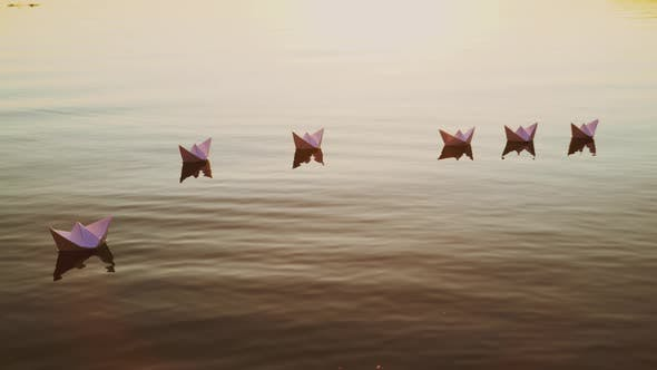 Thumbnail for White Paper Boats Float in the Lake Water at Sunset