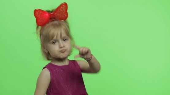 Mädchen in lila Kleid Tanzen und zeigt einen Finger nach vorne. Glückliches Kind. Chroma-Taste