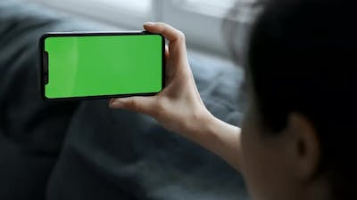Close Up A Woman's Hand Holds A Smartphone With A Green Screen For Chromakey