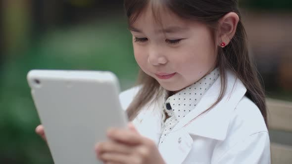 Thumbnail for Sweet Little Girl Playing on Digital Tablet Outdoors