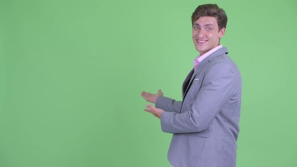 Thumbnail for Happy Young Businessman Showing Something To the Back