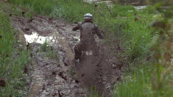 Thumbnail for Man rides motorcycle through mud in slow motion, shot on Phantom Flex 4K
