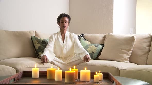 Thumbnail for Woman on sofa meditating with candles
