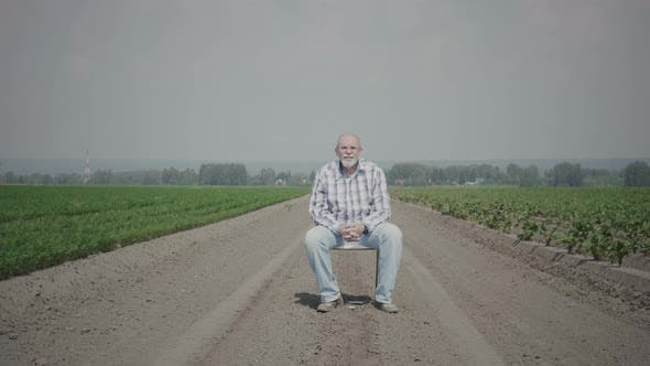 Thumbnail for Senior man sits on a chair in the field
