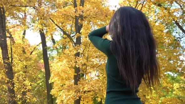 Thumbnail for A Young Asian Woman Fixes Her Hair in A Park