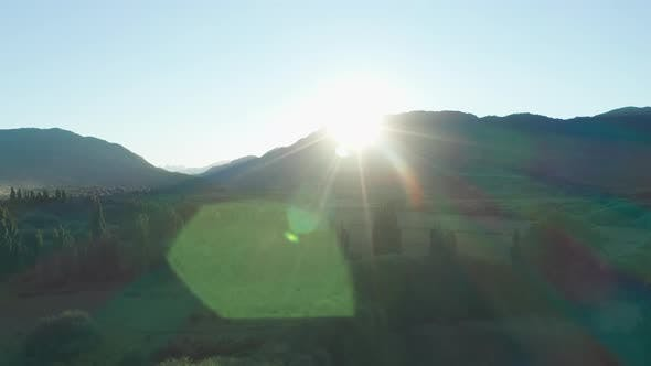 Drone Towards Mountains With Glowing Sun