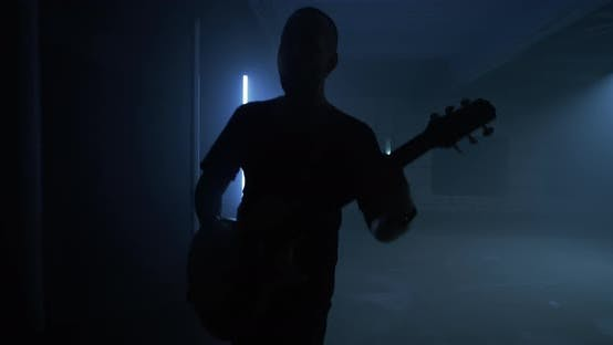 Energetic Male Rocker Playing Guitar Near Lamps