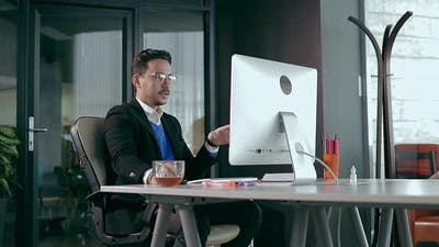 Businessman in Office in Front of Computer Showing Happy Emotions