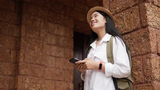 Traveler woman typing on phone while standing at ancient temple