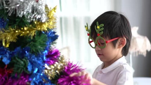 Asian Child Hanging Decorative Toy Together On Christmas Tree