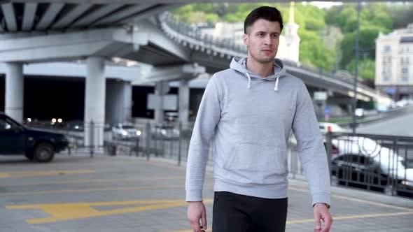 Thumbnail for Close Up of Modern Sports Man Wearing Grey Jacket Walking Through Urban City