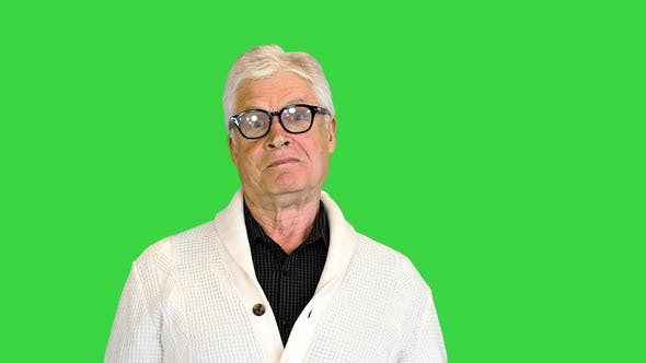 Happy Aged Man Shows a Greeting Sign on a Green Screen Chroma Key