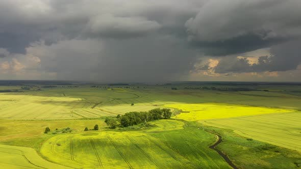 The storm clouds over the agricultural fields, view from a drone