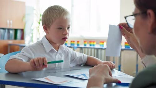 Life with Disabilities Boy with Downs Syndrome Studying Mathematics with Teacher Sitting at Desk in
