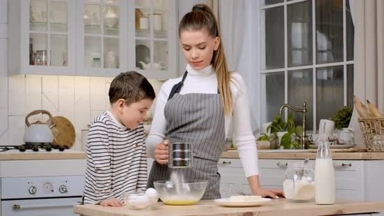 Young Mother in Apron Preparing Dough at Kitchen Her Curious Son Watching Process Slow Motion
