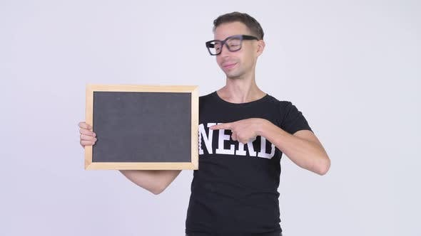 Thumbnail for Studio Shot of Happy Nerd Man Showing Blackboard and Giving Thumbs Up