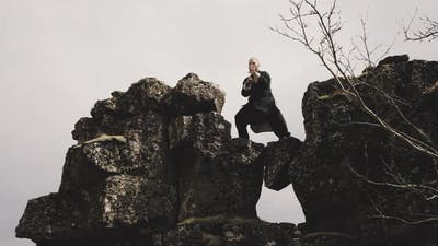 Kung Fu Master Performing Martial Arts On Rocks