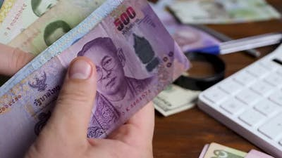 Male Hand Counts Thailand Baht or THB