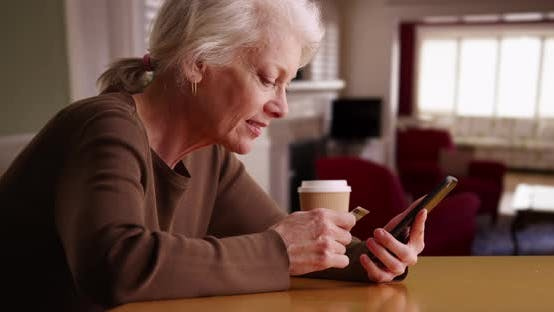 Cheerful senior woman using credit card and smart phone to make payment online