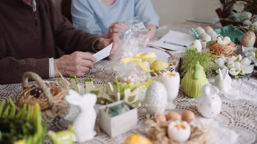 Grandfather and Granddaughter Writing Easter Cards Greetings To Loving Family.