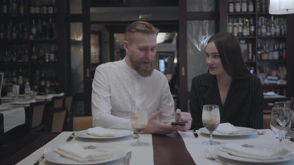 Thumbnail for Attractive Bearded Man and Pretty Brunette Woman Sitting in the Restaurant at the Table