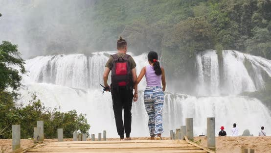 Thumbnail for Couple Walking Towards the Majestic Waterfall in the Border of Vietnam and China