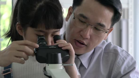 Doctor and kid girl looking microscope
