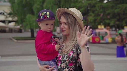 Happy Maman tient dans ses bras, puis jette son fils vers le haut.